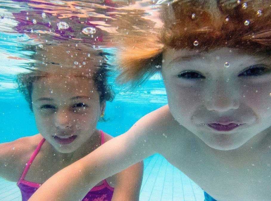 Photo of kids swimming underwater
